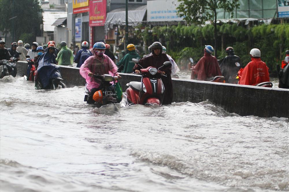 Nước ngập lút bánh xe máy trên đường Phạm Văn Đồng. Ảnh: M.Q