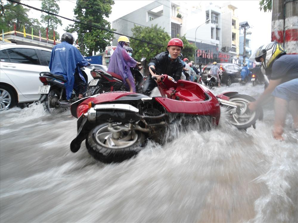 Mưa lớn, nước chảy xiết cuốn trôi xe máy trên đường Võ Văn Ngân (quận Thủ Đức). Ảnh: Minh Quân